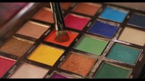 Paleta del maquillaje, cepillo de la inmersión en color anaranjado almacen de metraje de vídeo