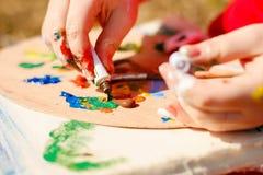 A paleta do artista com pinturas e escovas Fotografia de Stock