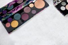 A paleta do cosmético multicolorido compõe com um espelho, paleta da sombra para os olhos, textura colorida das sombras, lugar pa imagens de stock