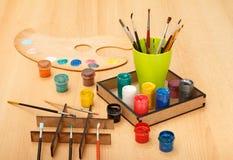 Paleta e caixa com pinturas e o copo coloridos com pincéis Fotos de Stock Royalty Free