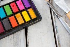 Paleta e pincéis coloridos na superfície de madeira Foto de Stock Royalty Free