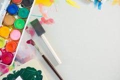 Paleta e pincéis coloridos no fundo branco Fotografia de Stock