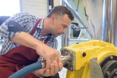 Paleta joven de la fijación del mecánico en el tractor fotografía de archivo