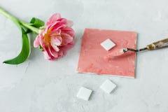 Paleta nóż na brezentowym obrazie z tulipanowym kwiatem i mozaika na szarym backround obraz stock