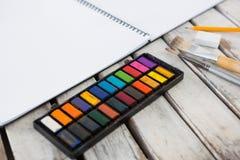 Paleta, pincéis e livro coloridos na superfície de madeira Fotografia de Stock Royalty Free