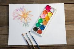 Paleta, pincéis e papel coloridos na superfície de madeira Imagens de Stock