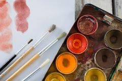 Paleta, pincéis e papel coloridos na superfície de madeira Imagem de Stock