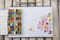 Paleta, pincéis e papel coloridos na superfície de madeira Fotografia de Stock