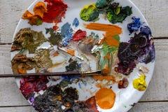Paleta y cepillo del arte con las porciones de pintura de los colores, de la témpera y de aceite foto de archivo libre de regalías