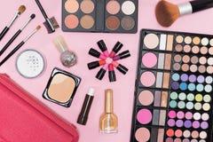 Paleta y cepillos de los cosméticos del maquillaje del primer en fondo rosado Fotos de archivo