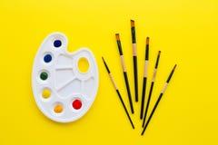 Paleta y cepillos en fondo amarillo imágenes de archivo libres de regalías