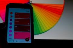 Paletas de colores electr?nicas entre un smartphone y un ordenador port?til imagenes de archivo