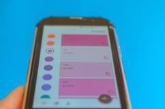 Paletas de cores eletr?nicas entre o smartphone e o fundo azul imagens de stock royalty free