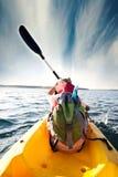 Paletas jovenes del muchacho a través de las aguas del mar con su canoa Imágenes de archivo libres de regalías