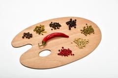 Palett av olika kryddor på träpaletten som isoleras på vit Royaltyfri Foto