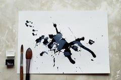 Palett av svartvit målarfärg ett ark av vitt konstpapper med svart färgfärgpulver Fotografering för Bildbyråer