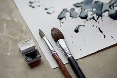 Palett av svartvit målarfärg ett ark av vitt konstpapper med svart färgfärgpulver Arkivfoto