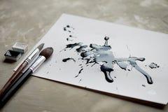 Palett av svartvit målarfärg ett ark av vitt konstpapper med svart färgfärgpulver Arkivbild