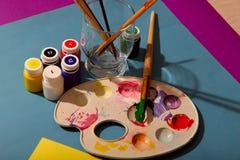 Palett med borstar och målarfärger på en blå bakgrund arkivfoton