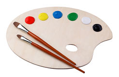Palette. Wooden palette with paints and brushes on white background Stock Image