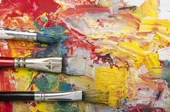 Palette with acrylic primary colors. Primary acrylic colors on a dirty palette with a spatula and brushes stock images