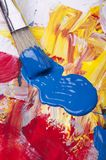 Palette with acrylic primary colors. Primary acrylic colors on a dirty palette with a spatula and brushes stock photo