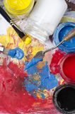 Palette with acrylic primary colors. Glass jars with acrylic primary colors and a dirty palette with a spatula and brushes royalty free stock photography