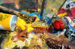 Palette of the artist with tubes of paint and brushes. Closeup Stock Photo