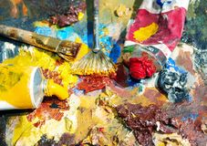 Palette of the artist with tubes of paint and brushes. Royalty Free Stock Photos