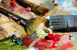 Palette of the artist with tubes of paint and brushes. Closeup Royalty Free Stock Photos