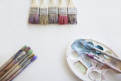 The palette with bright colors and brushes. On the white background Stock Image