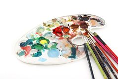 Palette and brushes. Painter palette with brushes on a white background Stock Image