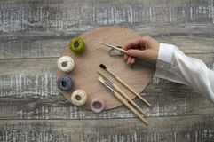 Palette with brushes and balls of cotton threads on the wooden table Royalty Free Stock Photo