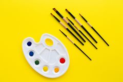 Palette and brushes on yellow background. royalty free stock image