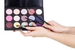 Palette colorful eye shadow, cosmetic brushes in female hands isolated . Royalty Free Stock Photography