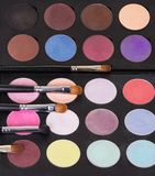 A palette of colorful eye shadow and cosmetic brushes. Stock Photos