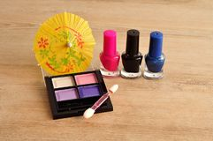 A palette of colorful eye shadow displayed with a row of nail polish. On a wooden background stock image