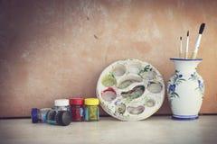 Palette de couleurs et pinceau d'affiche dans un vase Image stock