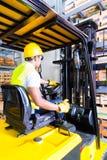Palette de levage de chauffeur de camion asiatique de chariot élévateur dans le stockage Image stock