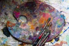 Palette de peintre de lieu de travail avec des couleurs et des brosses Palette de couleurs, désordre créatif, art Photos stock