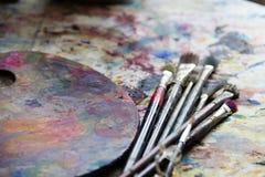 Palette de peintre de lieu de travail avec des couleurs et des brosses Palette de couleurs, désordre créatif, art Photo libre de droits
