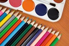 Palette de peintres avec le balai et les crayons Image stock