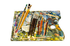 Palette de peintres de pétrole avec des balais sur le blanc Photographie stock libre de droits