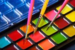 Palette des peintures d'aquarelle avec trois balais Photographie stock libre de droits