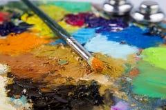 Palette en bois d'art avec des gouttes de peinture et d'une brosse sur le fond blanc Image stock