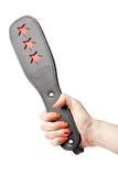 Palette en cuir noire de fétiche dans la main femelle d'isolement sur le blanc Photo stock