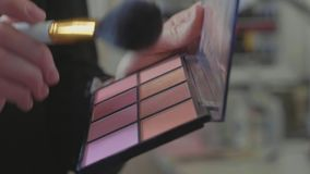A palette with eye shadows and a makeup brush: women`s cosmetics.