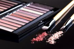 Palette of eyeshadow and two brushes on black background. Set of cosmetics. On dark royalty free stock images