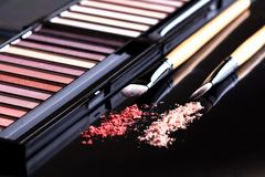 Palette of eyeshadow and two brushes on black background. Set of cosmetics. On dark stock images