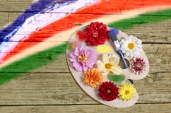Palette with flowers. Palette with multi-colored flowers against the painted old boards